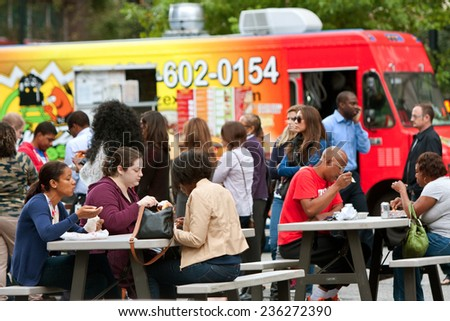 "ATLANTA, GA - OCTOBER 16:  Customers sit and eat meals from popular food trucks during their lunch hour, at ""Food Truck Thursday"" on October 16, 2014 in Atlanta. - stock photo"