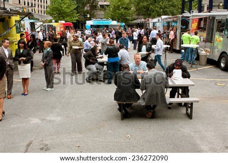 "ATLANTA, GA - OCTOBER 16:  Customers stand in line to buy meals from popular food trucks and eat during their lunch hour, at ""Food Truck Thursday"" on October 16, 2014 in Atlanta. - stock photo"