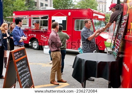 "ATLANTA, GA - OCTOBER 16:  Customers stand in line to order meals from a popular food truck during their lunch hour, at ""Food Truck Thursday"" on October 16, 2014 in Atlanta. - stock photo"