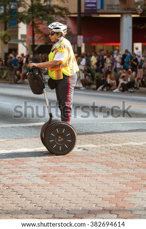 ATLANTA, GA - SEPTEMBER 5:  A security officer uses a Segway device to move around the crowd before the annual Dragon Con parade begins on September 5, 2015 in Atlanta, GA.  - stock photo