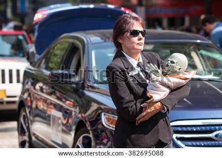 ATLANTA, GA - SEPTEMBER 5:  A woman dressed like a Men In Black agent carries an alien baby while walking in the annual Dragon Con Parade on September 5, 2015 in Atlanta, GA.  - stock photo