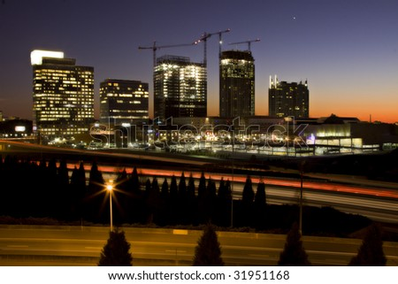 Atlanta skyline at sunset with traffic streaks and construction cranes - stock photo