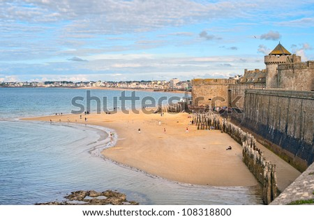 Atlantic beach under the towers of city walls in St Malo, Brittany, France - stock photo