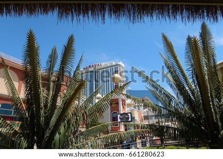 ATLANTIC CITY, NEW JERSEY - JUNE 11, 2017: Trump Taj Mahal framed by palm trees and part of a thatched roof. Editorial use only.
