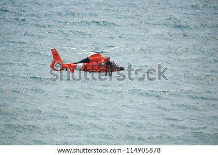 ATLANTIC CITY, NJ - AUGUST 24: US Coast Guard HH-65A Dolphin helicopter drops rescue diver during rescue exercise August 24, 2011 in Atlantic City, New Jersey - stock photo