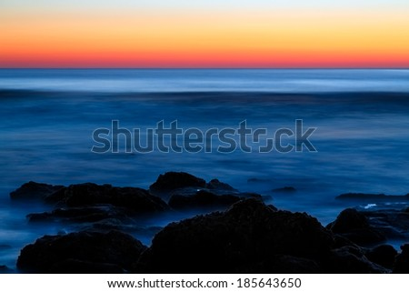 Atlantic ocean waves break on a coquina stone at Florida's Washington Oaks State Park in northern Flagler County just before sunrise. - stock photo
