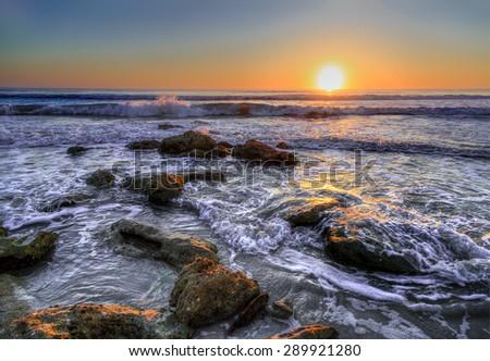 Atlantic ocean waves break on a coquina stone beach at Florida's Washington Oaks State Park at sunrise. - stock photo