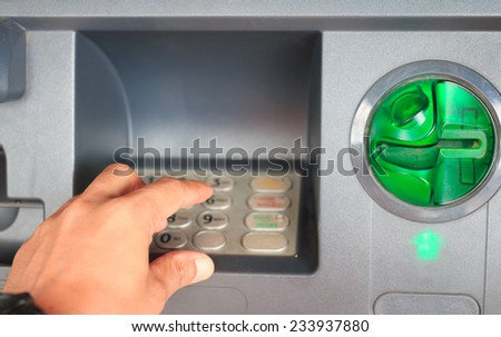 ATM close-up with male hand - stock photo