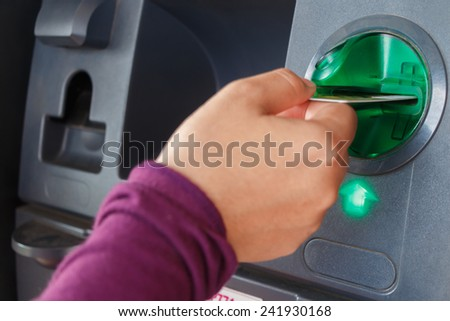 ATM close-up with woman hand - stock photo