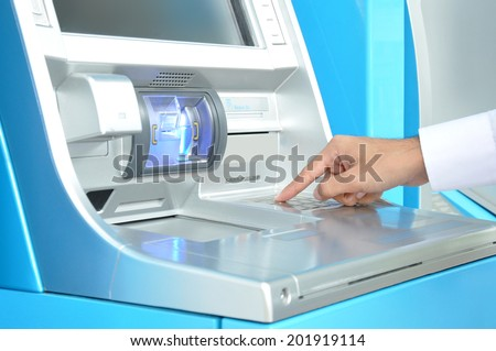 ATM (or Automated Teller Machine ) with hand pressing on the keypad - stock photo