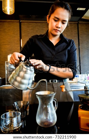 Atmosphere of cafe bar. Lovely barista with her drip coffee, smell and equipment. Selected focus.