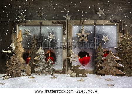 Atmospheric and romantic christmas window decoration with red candles, snow and wood. - stock photo