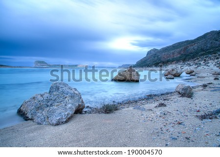 Atmospheric blue beach background with rocky boulders dotted along a deserted tropical beach in Crete, Greece on a cloudy overcast day, long exposure image - stock photo