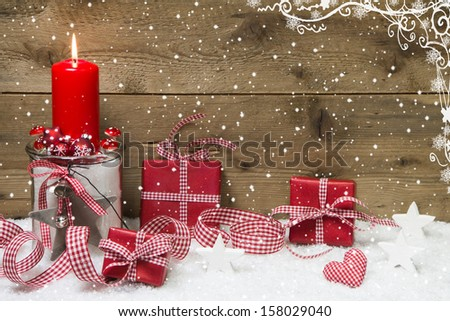 Atmospheric Christmas card with red burning candle and presents on snowflake wooden background - stock photo