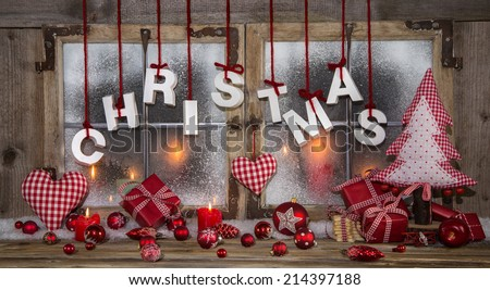 Atmospheric christmas decoration in a window in red and white colors with burning candles. - stock photo