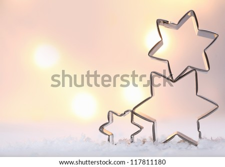 Atmospheric Christmas star background with three metal star cookie cutters balanced on top of each other on snow against a soft moody bokeh of glowing lights with copyspace - stock photo