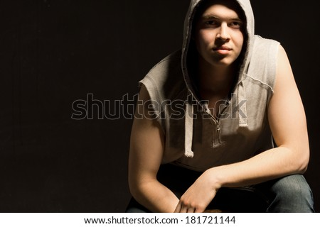 Atmospheric dark portrait of a fit young man sitting down leaning forwards with a serious expression and intense look, with copyspace