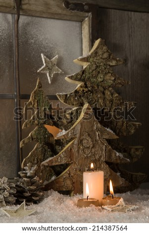 Atmospheric natural christmas decoration with wood and burning candles. - stock photo