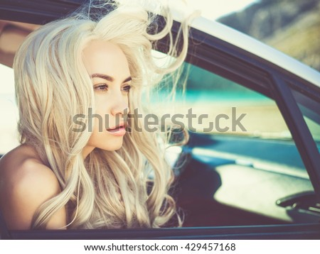 Atmospheric outdoors fashion portrait of beautiful blonde in car on the beach - stock photo