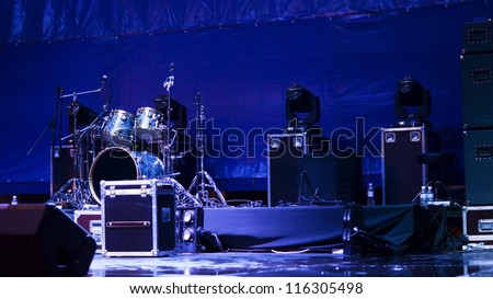 Atmsopheric background with a set of drums and speakers set up on a stage in blue light ready for a band to give a performance - stock photo