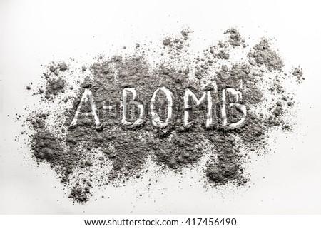 Atom bomb word written in grey explosion ash, dust cloud - stock photo