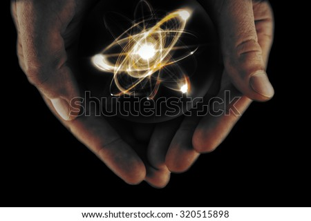 Atomic orbitting particle being held in cupped hands - stock photo