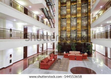 Atrium with red armchairs, couches and elevators in stylish hotel. - stock photo