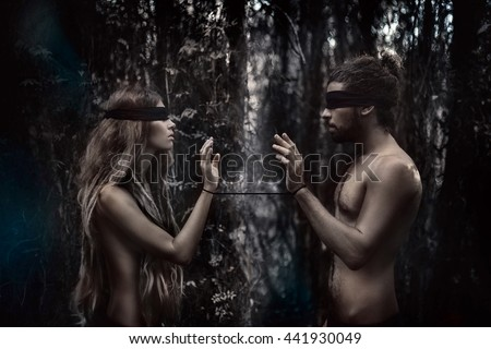 atrractive young man and woman with eyes closed. lost in forest concept