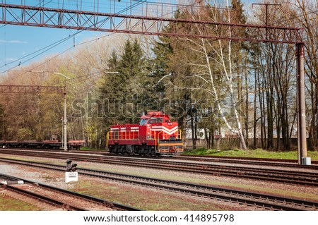 attached diesel locomotive is pulling freight wagons, spring - stock photo