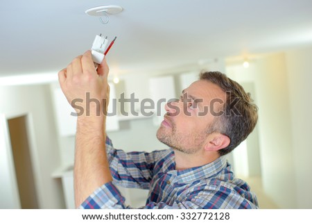 Attaching a smoke alarm to the ceiling - stock photo