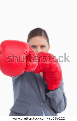 Attacking fist of tradeswoman in boxing glove against a white background