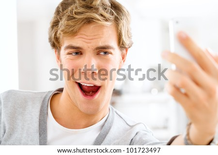 Attactive young man taking self portrait using mobile phone is a