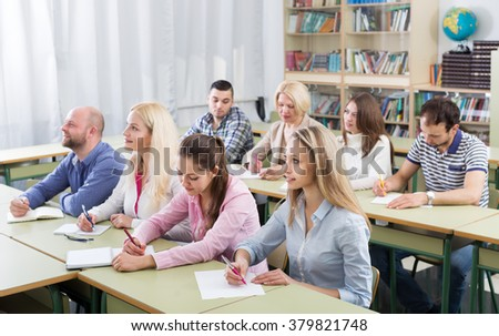 Attentive adult students industriously writing down the summary in the classroom  - stock photo