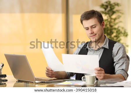Attentive businessman working comparing paper documents sitting in a desk at office  - stock photo