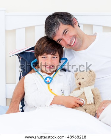 Attentive father and his sick son playing with a stethoscope sitting on a bed - stock photo