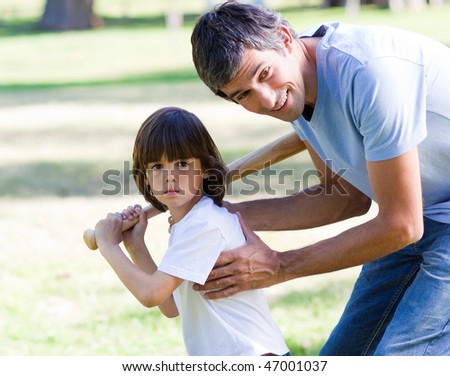 Attentive father playing baseball with his son in the park - stock photo
