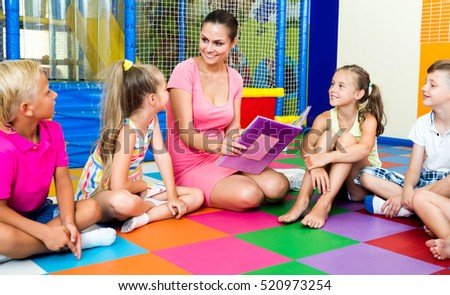 Attentive kids sitting around young smiling teacher reading book in class