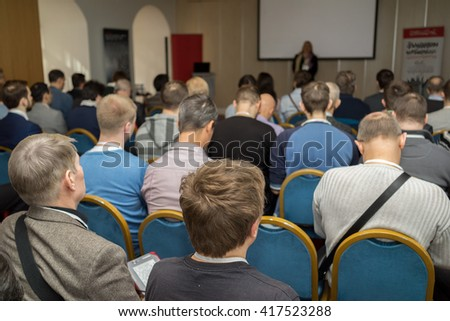 Attentive listeners look at stage at business conference - stock photo