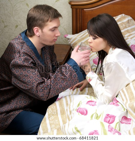 Attentive man give fresh water to sick woman at the bed - stock photo
