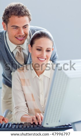 Attentive manager helping his colleague working at a computer in an office
