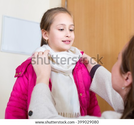 Attentive mother dresses her child to go outdoors. She ties a warm wool scarf around her child's neck - stock photo