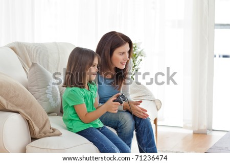 Attentive mother encouraging her daughter playing video games in the living room