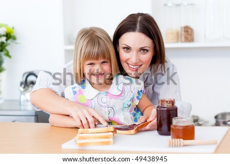 Attentive mother helping her daughter prepare the breakfast in the kitchen - stock photo