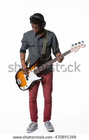 Attentive musician plays the electric guitar and looks on his favorite expensive musical instrument. Full body shot. Isolated.