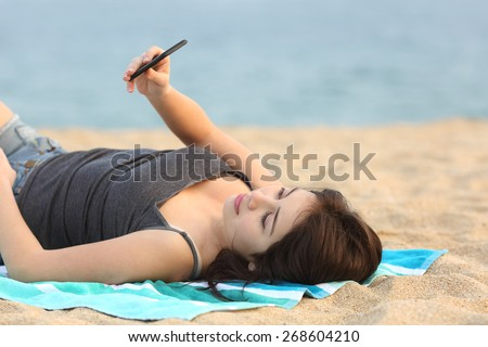 Attentive teen girl lying and using a smart phone on the sand of the beach - stock photo