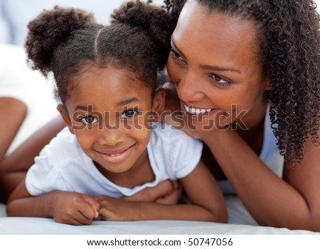 Attentive woman and her daughter relaxing lying down on bed at home