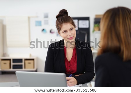 attentive young businesswoman listening to female colleague - stock photo
