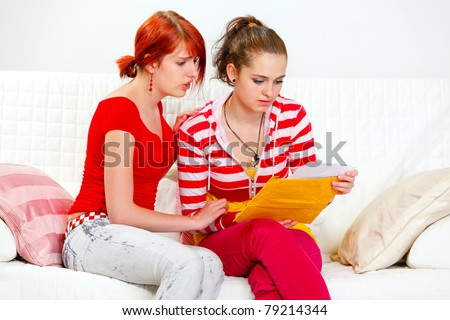 Attentive young girl soothing reading letter with bad news girlfriend - stock photo
