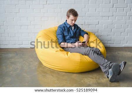 attentive young man sitting in yellow bean bag chair and using black smart phone indoors - Black Bean Bag Chair