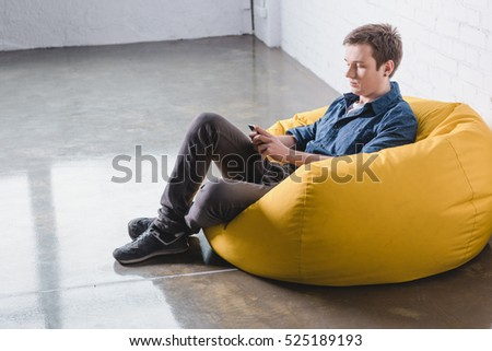 Etonnant Attentive Young Man Sitting In Yellow Bean Bag Chair And Using Black  Smartphone Indoors